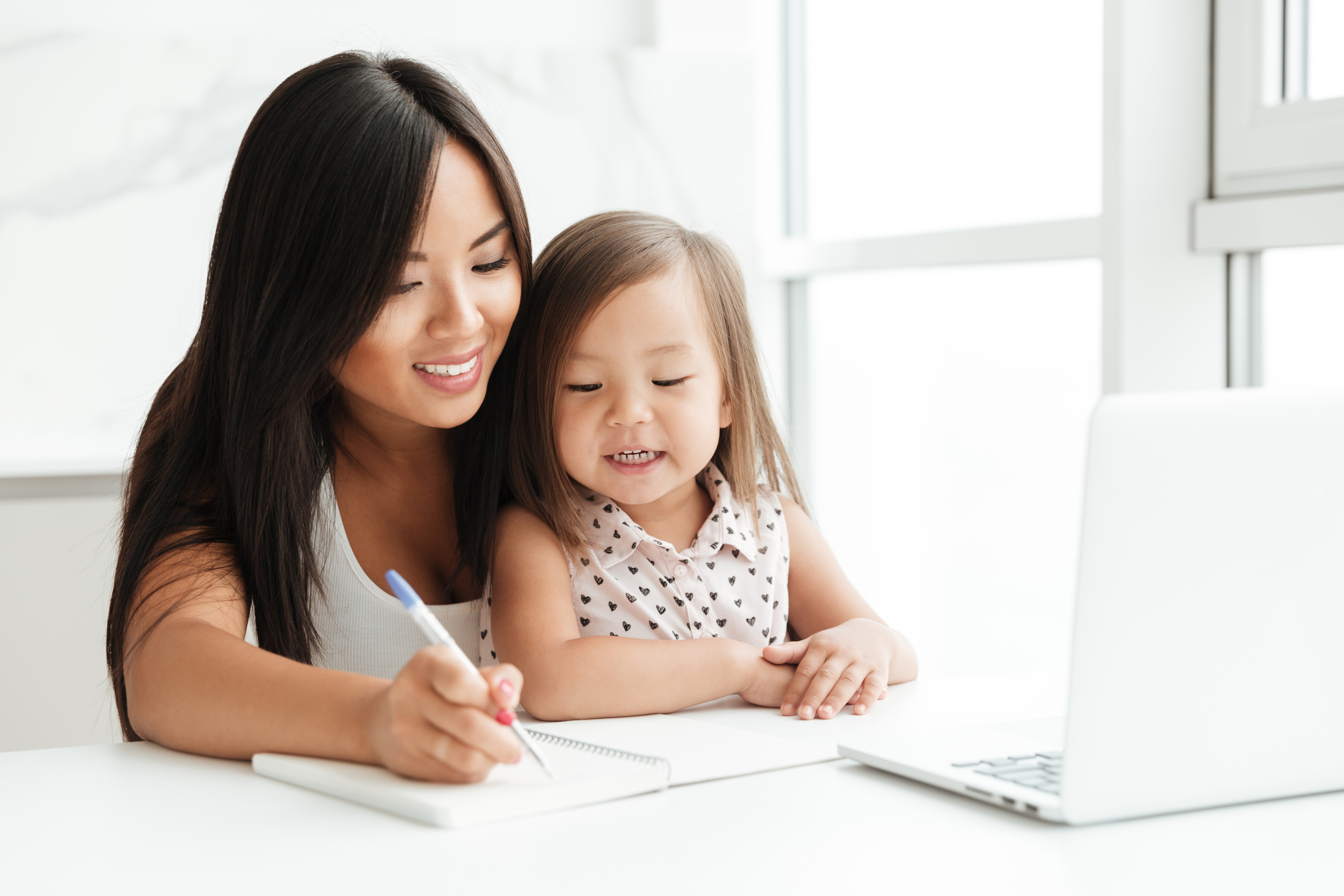 storyblocks-image-of-amazing-young-mom-sitting-at-the-table-with-little-cute-asian-girl-at-home-indoors-using-laptop-computer-writing-notes-to-notebook-looking-aside_H0lMSChT9W
